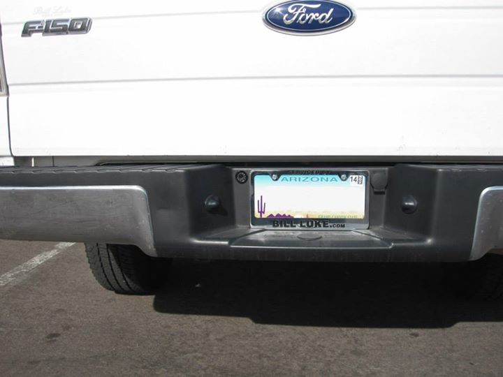 Through hole camera with IR transmitters installed to left of license plate.